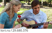 Купить «A man serenades his girlfriend with a song as she holds a rose as they look at the camera», видеоролик № 29680376, снято 17 ноября 2011 г. (c) Wavebreak Media / Фотобанк Лори