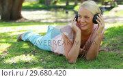 Купить «A woman moves her head to the rhythm of the music as she listens to headphones», видеоролик № 29680420, снято 17 ноября 2011 г. (c) Wavebreak Media / Фотобанк Лори