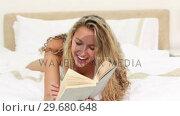 Купить «Blonde haired woman laughing while reading», видеоролик № 29680648, снято 11 ноября 2011 г. (c) Wavebreak Media / Фотобанк Лори