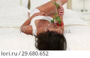 Купить «Brunette haired woman smelling a rose», видеоролик № 29680652, снято 11 ноября 2011 г. (c) Wavebreak Media / Фотобанк Лори