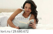 Купить «Brunette haired woman reads a book», видеоролик № 29680672, снято 11 ноября 2011 г. (c) Wavebreak Media / Фотобанк Лори