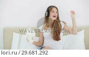 Купить «Young blonde woman listening to music with her headphones», видеоролик № 29681292, снято 23 ноября 2011 г. (c) Wavebreak Media / Фотобанк Лори
