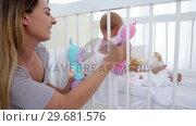 Купить «Woman playing dolls with her baby», видеоролик № 29681576, снято 25 ноября 2011 г. (c) Wavebreak Media / Фотобанк Лори