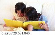 Купить «Girl talking to her sister as they read a book together», видеоролик № 29681840, снято 25 ноября 2011 г. (c) Wavebreak Media / Фотобанк Лори