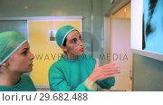 Купить «Medical team examining a Xray», видеоролик № 29682488, снято 24 апреля 2012 г. (c) Wavebreak Media / Фотобанк Лори