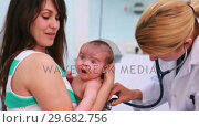 Купить «Mother with a newborn in her arms in an examination room with a doctor using a stethoscope», видеоролик № 29682756, снято 27 апреля 2012 г. (c) Wavebreak Media / Фотобанк Лори