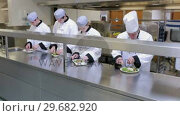 Купить «Cooks garnishing plates in a kitchen», видеоролик № 29682920, снято 1 августа 2012 г. (c) Wavebreak Media / Фотобанк Лори