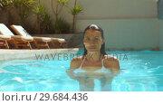 Купить «Attractive woman in swimming pool walking toward the camera», видеоролик № 29684436, снято 25 марта 2013 г. (c) Wavebreak Media / Фотобанк Лори