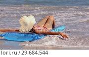 Купить «Girl sunbathing on a lilo on the beach getting splashed by the waves», видеоролик № 29684544, снято 3 апреля 2013 г. (c) Wavebreak Media / Фотобанк Лори