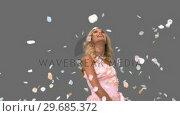 Купить «Pretty woman in ballgown admiring petals falling on grey screen», видеоролик № 29685372, снято 8 апреля 2013 г. (c) Wavebreak Media / Фотобанк Лори