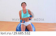 Fit brunette sitting on an exercise ball and lifting weights. Стоковое видео, агентство Wavebreak Media / Фотобанк Лори