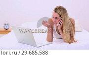 Happy gorgeous blonde lying on bed phoning and using laptop. Стоковое видео, агентство Wavebreak Media / Фотобанк Лори