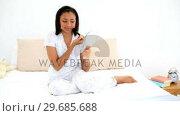 Beautiful young woman applying make up sitting on her bed. Стоковое видео, агентство Wavebreak Media / Фотобанк Лори