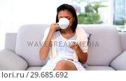 Купить «Beautiful calm woman drinking of cup sitting on couch», видеоролик № 29685692, снято 14 июня 2013 г. (c) Wavebreak Media / Фотобанк Лори