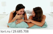 Купить «Attractive chatting women lying on bed», видеоролик № 29685708, снято 14 августа 2013 г. (c) Wavebreak Media / Фотобанк Лори