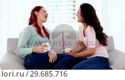 Купить «Beautiful amused women sitting on couch while having a conversation», видеоролик № 29685716, снято 15 августа 2013 г. (c) Wavebreak Media / Фотобанк Лори