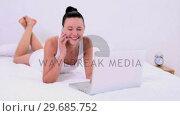Купить «Beautiful woman phoning while using her notebook», видеоролик № 29685752, снято 18 июля 2013 г. (c) Wavebreak Media / Фотобанк Лори