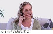 Купить «Happy woman phoning with her smartphone sitting on couch», видеоролик № 29685812, снято 31 мая 2013 г. (c) Wavebreak Media / Фотобанк Лори