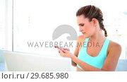 Купить «Smiling fit woman sending a text», видеоролик № 29685980, снято 5 июня 2013 г. (c) Wavebreak Media / Фотобанк Лори