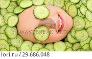 Купить «Smiling womans face surrounded by cucumber slices », видеоролик № 29686048, снято 23 июля 2013 г. (c) Wavebreak Media / Фотобанк Лори