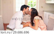 Купить «Happy couple kissing at the table», видеоролик № 29686696, снято 12 декабря 2013 г. (c) Wavebreak Media / Фотобанк Лори