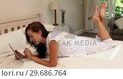 Купить «Pretty woman lying on her bed using tablet pc», видеоролик № 29686764, снято 13 декабря 2013 г. (c) Wavebreak Media / Фотобанк Лори