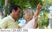 Купить «Smiling couple pointing on a sunny day», видеоролик № 29687356, снято 3 февраля 2016 г. (c) Wavebreak Media / Фотобанк Лори