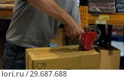 Купить «Worker sealing cardboard box with packing tape», видеоролик № 29687688, снято 17 октября 2015 г. (c) Wavebreak Media / Фотобанк Лори
