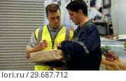 Купить «Man delivering courier to warehouse worker», видеоролик № 29687712, снято 17 октября 2015 г. (c) Wavebreak Media / Фотобанк Лори