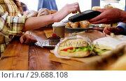 Купить «Customer making payment through payment terminal machine at counter», видеоролик № 29688108, снято 30 мая 2016 г. (c) Wavebreak Media / Фотобанк Лори