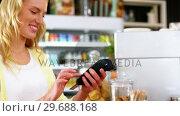 Купить «Customer making payment through payment terminal machine at counter», видеоролик № 29688168, снято 30 мая 2016 г. (c) Wavebreak Media / Фотобанк Лори