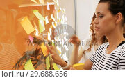 Купить «Female business executives interacting while reading sticky notes», видеоролик № 29688656, снято 5 июля 2016 г. (c) Wavebreak Media / Фотобанк Лори