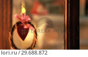Купить «Wreath with heart shape decoration hanging on door», видеоролик № 29688872, снято 31 августа 2016 г. (c) Wavebreak Media / Фотобанк Лори