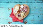 Купить «Christmas cookies with napkin on heart shape wooden board», видеоролик № 29688932, снято 30 августа 2016 г. (c) Wavebreak Media / Фотобанк Лори