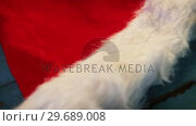 Купить «Santa hat and snowflake on wooden plank», видеоролик № 29689008, снято 30 августа 2016 г. (c) Wavebreak Media / Фотобанк Лори