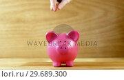 Купить «Hand dropping coin into piggy bank», видеоролик № 29689300, снято 8 июня 2016 г. (c) Wavebreak Media / Фотобанк Лори