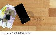 Купить «Mobile phone, currency, coins and car key», видеоролик № 29689308, снято 8 июня 2016 г. (c) Wavebreak Media / Фотобанк Лори