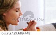 Купить «Woman eating breakfast in living room», видеоролик № 29689448, снято 26 августа 2016 г. (c) Wavebreak Media / Фотобанк Лори