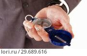 Купить «Businessman holding direction compass», видеоролик № 29689616, снято 24 августа 2016 г. (c) Wavebreak Media / Фотобанк Лори
