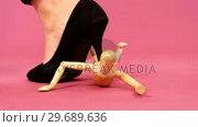 Купить «Female foot with black stiletto stamping a figurine», видеоролик № 29689636, снято 24 августа 2016 г. (c) Wavebreak Media / Фотобанк Лори