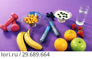 Купить «Dumbbells, banana, water glass, fruit, skipping rope and breakfast», видеоролик № 29689664, снято 24 августа 2016 г. (c) Wavebreak Media / Фотобанк Лори