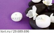 Купить «Close-up of pebble stones with flowers and candles», видеоролик № 29689696, снято 24 августа 2016 г. (c) Wavebreak Media / Фотобанк Лори