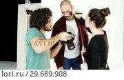 Купить «Model getting face make-up while interacting with photographer», видеоролик № 29689908, снято 1 сентября 2016 г. (c) Wavebreak Media / Фотобанк Лори