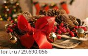 Купить «Grapevine wreath with red ribbon and pine cone», видеоролик № 29690056, снято 31 августа 2016 г. (c) Wavebreak Media / Фотобанк Лори