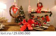 Купить «Grapevine wreath with red ribbon and pine cone», видеоролик № 29690060, снято 31 августа 2016 г. (c) Wavebreak Media / Фотобанк Лори