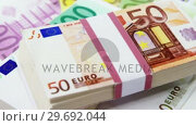 Купить «Bundle of 50 and 100 euro dollar», видеоролик № 29692044, снято 12 августа 2016 г. (c) Wavebreak Media / Фотобанк Лори