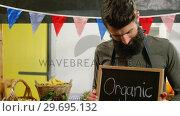 Купить «Male staff holding organic sign board», видеоролик № 29695132, снято 4 октября 2016 г. (c) Wavebreak Media / Фотобанк Лори