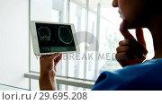 Купить «Beautiful surgeon examining report on digital tablet», видеоролик № 29695208, снято 6 ноября 2016 г. (c) Wavebreak Media / Фотобанк Лори
