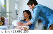 Купить «Couple with their newborn baby in ward», видеоролик № 29695256, снято 6 ноября 2016 г. (c) Wavebreak Media / Фотобанк Лори