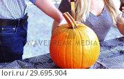 Купить «Man carving a pumpkin to make halloween lantern», видеоролик № 29695904, снято 12 сентября 2016 г. (c) Wavebreak Media / Фотобанк Лори
